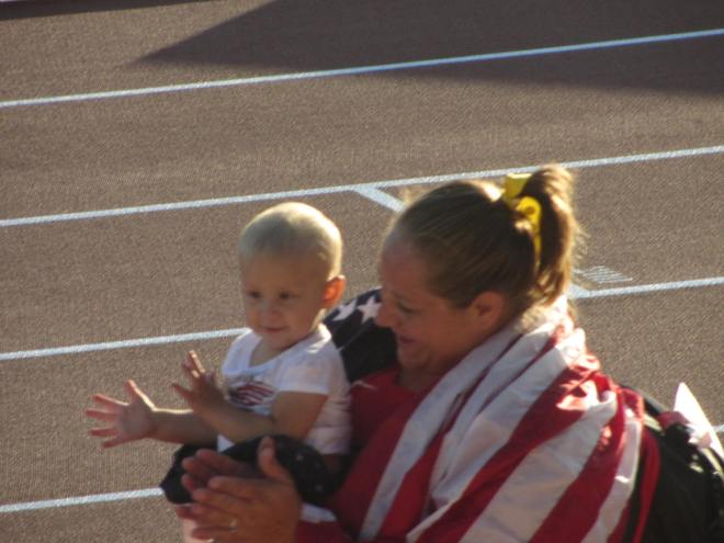 Jillian Camarena-Williams and her son clap along with the crowd after she won the silver medal in shot put.